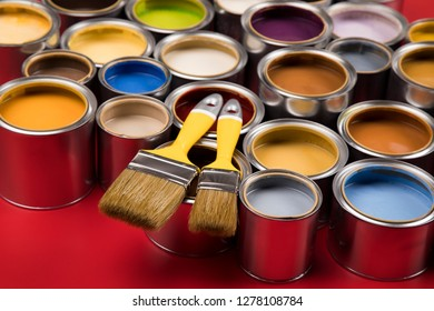 Open buckets with a paint and brush, red background