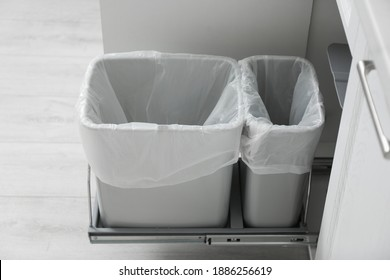 Open cabinet with empty trash bins for separate waste collection in kitchen