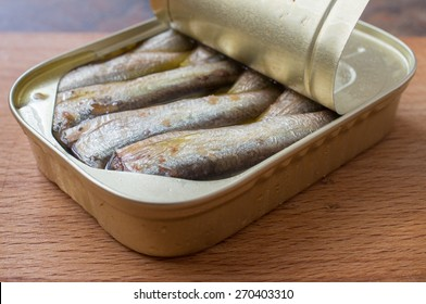 Open can of sardines on a wooden board