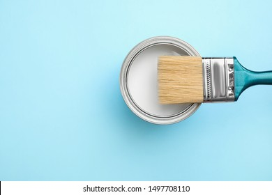 Open can with white paint and brush on blue background, top view. Space for text
