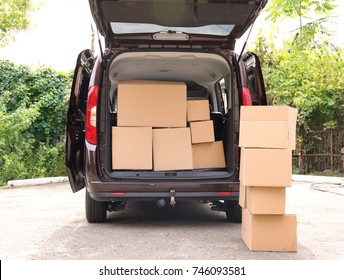 Open car trunk and moving boxes outdoors