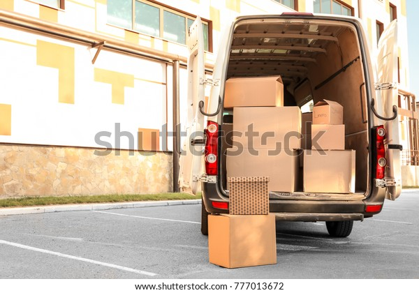 Open car trunk with moving boxes outdoors