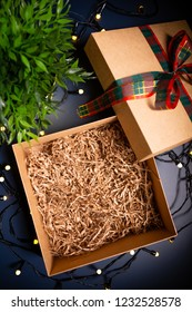 Open carton present box with ribbon on blue background surrounded by decorative lights. Christmas theme.