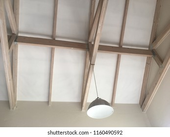 Open Ceiling White Washed Trusses with an Industrial Lamp Shade
