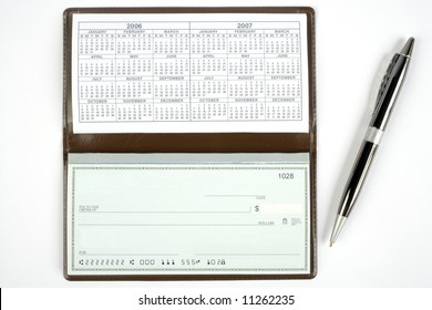 An open checkbook showing the calendar with a pen to the right side.