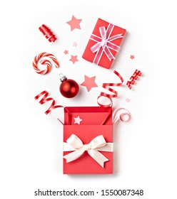 Open Christmas surprise gift box with ribbon exploding festive red on a white background.