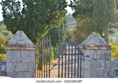 Open church gate with a cross with a path between lines of trees