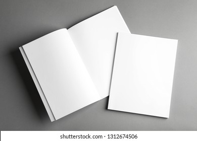 Open and closed blank brochures on grey background, top view. Mock up for design
