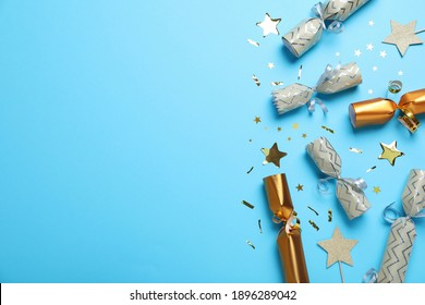 Open and closed Christmas crackers with shiny confetti on light blue background, flat lay. Space for text