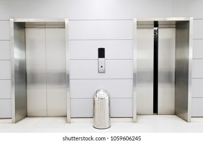 Open and closed chrome metal office building elevator doors realistic photo.The trash in front of the elevator.