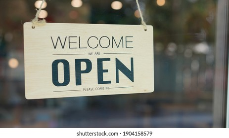 Open and closed flip sign in front of coffee shop and restaurant glass door. Wooden sign with wording of place's status. Say Welcome. We're OPEN. Please come in.