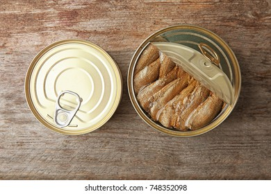 Open and closed tin cans with fish on wooden background