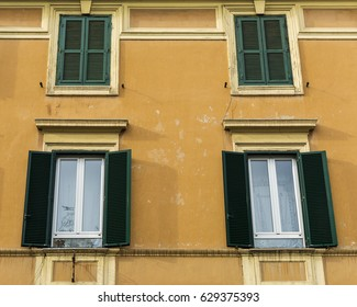 Open and closed window shutters of an old building in Rome, Italy