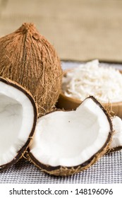 A open coconut with grated coconut in the background.