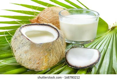 Open coconut with milk inside on palm leaf.