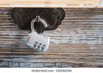 Open combination lock on a wooden box