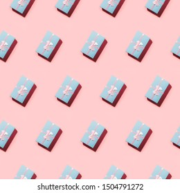 Open composition of blue pastel gift boxes on pink in diagonal.