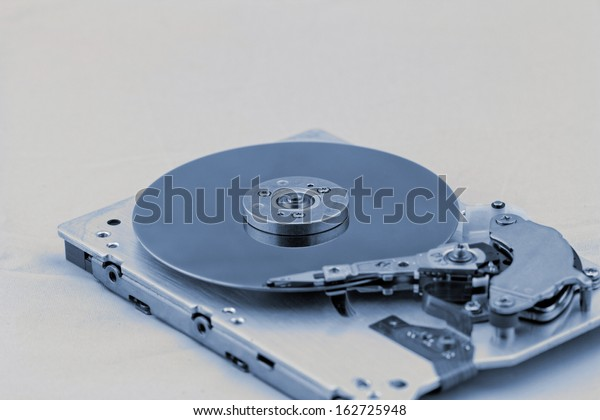 Open computer hard drive on white background with blue