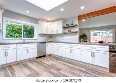 Open concept kitchen with white cabinets, grey quartz countertops and tile backsplash.