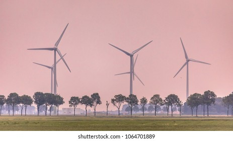 Open countryside with trees and wind turbines at orange sunset
