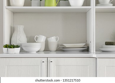 Open cupboard with clean dishes in kitchen