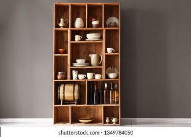 Open cupboard with clean dishes near color wall in kitchen