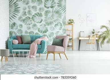 Open deign of modern apartment with turquoise couch in the living room and workspace against white wall