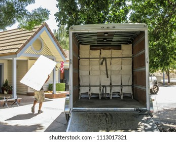 Open delivery van with tables and chairs for event.