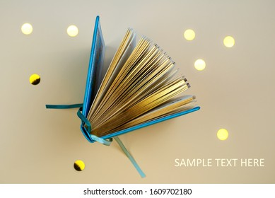 An open diary or a book with gold pages. On a beige background with scattered sequins.