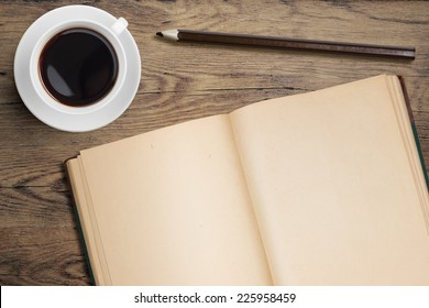 Open diary and coffee cup on old wooden table