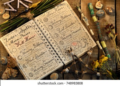 Open diary with lunar spells, pentagram and magic wands on witch table. Occult, esoteric, divination and wicca concept. Halloween vintage background