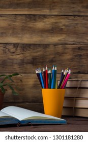 Open Diary, A Pile of Books, Colored Pencils in a Plastic Glass, Flower in a Pot, on a Wooden Background