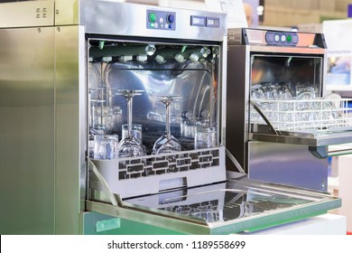 Open dishwasher with clean glass, cups, plates and dishes, selective focus