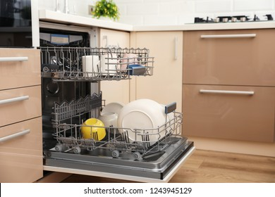 Open dishwasher with clean tableware in kitchen. Space for text