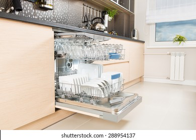 Open dishwasher with clean utensils in it.