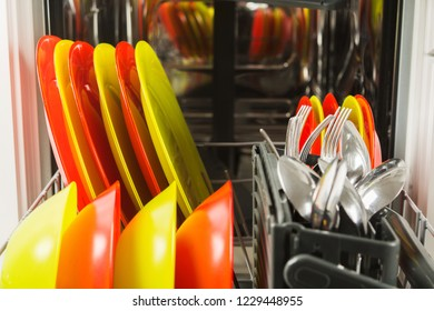 Open dishwasher with fresh clean dish and flatware, closeup view