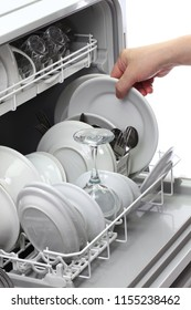 open dishwasher, man hand taking out clean dish, after washing