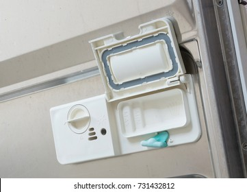 Open dispenser in a dishwasher with clean plates, cups and dishes - Selective focus