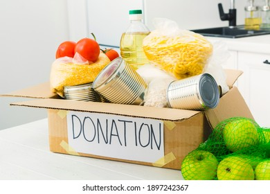 Open donation box with food in kitchen. Help for people. Charity concept