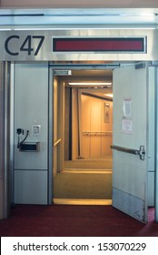 Open door to airplane boarding jetway