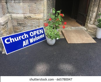 Open door to a church with a sign that reads: Church Open All Welcome
