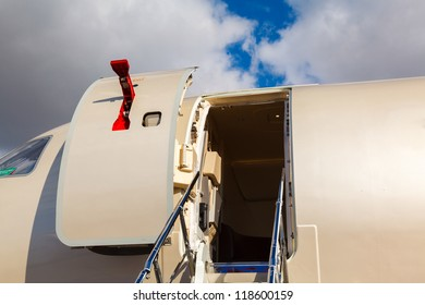 open door and cocpit in private jet against the blue sky