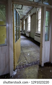 Open door and corridor at an abandoned and derelict lunatic asylum/hospital (now demolished), Cane Hill, Coulsdon, Surrey, England, UK