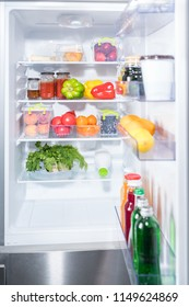 Open door of a fridge with fresh fruit and vegetables on the shelves and bottles of juice and beverage in the door