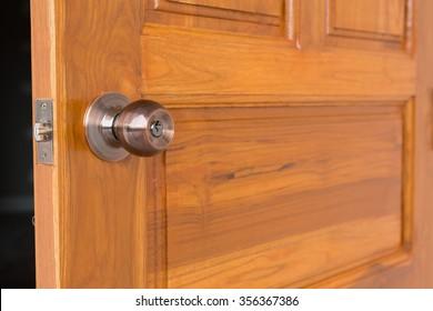 open door, door knob and keyhole on wooden door, close up image
