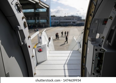 Open door to a large airliner as seen from the stairs.