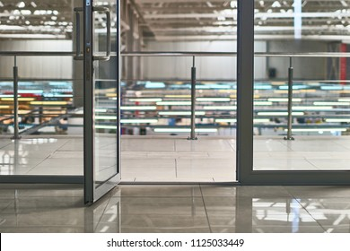 Open door in the modern office or shopping center in grey colors with bokeh background
