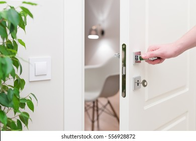 To open the door. Modern white door with chrome metal handle and a man's arm. Elements of interior closeup