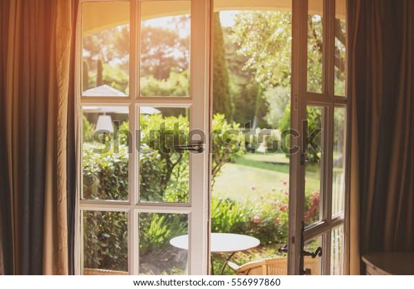 Offene Tür und Natur. Grüne Pflanzen und Sonnenlicht. Haus mit Garten.