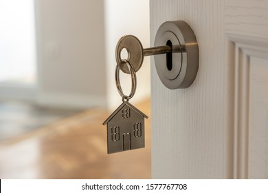 Open door to a new home with key and home shaped keychain. Mortgage, investment, real estate, property and new home concept